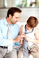 Portrait of a caring young father helping his son to wear tie at home