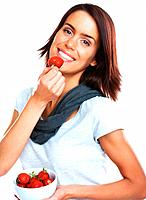 Portrait of a young woman eating a bowl of fresh strawberries against white background
