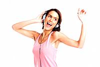 Young attractive woman dancing to music with headphones against white background