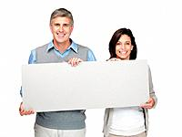 Portrait of a happy mature couple holding a blank billboard on white background