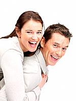 Portrait of happy young male piggybacking his cute girlfriend smiling against white background