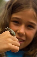 girl showing a frog sitting on the back of her hand, France