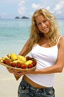 long_haired blond young woman presenting a plate of regional fruits on a tropical beach, Thailand, Krabi