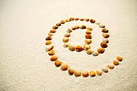 Shells on sand in shape of @ symbol