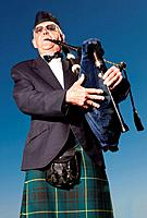 Mature highlander wearing kilt and playing bagpipes against blue sky