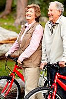 Portrait of a sporty mature couple walking with bicycle in countryside