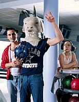 Three Young People at Bowling Alley with Man Wearing Goat Mask