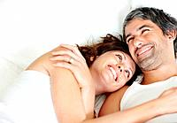 Portrait of cosy mature couple smiling together while lying on bed