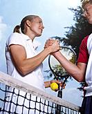Female and male tennis player shaking hands above net