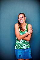 Portrait of pretty excited young woman standing against grey background and laughing