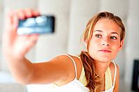 Portrait of a cute young woman taking picture of herself through her mobile phone