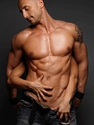 Woman´s hands touching young muscular man´s stomach