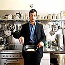 Man Wearing Suit Preparing Fried Egg in Kitchen