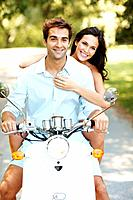 Portrait of beautiful young couple riding on moped in a park