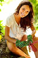 Closeup portrait ofan attractive young woman holding gardening tools and siiting outdoor in a garden