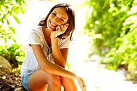 Portrait of sweet young woman sitting outdoors and smiling