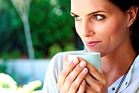 Closeup of a cute young woman looking away with a cup of coffe