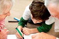 Adorable little boy making a drawing with his grandparents while lying on floor