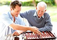 Portrait of father and son busy playing backgammon in a park