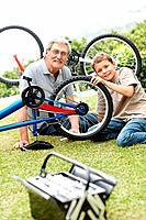 Little boy fixing a bicycle tyre with his grandfather and a toolbox lying on front in a park _ Outdoor
