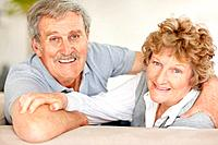 Portrait of sweet old couple looking behind while sitting on sofa _ Indoor