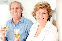Portrait of a happy old lady drinking wine with her husband