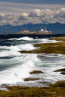 The lighthouse on Entrance Island stands out against a mountainous west coast backdrop amid a crashing surf onto Gabriola Island, Southern Gulf Island...