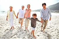 Portrait of a sweet family walking on the beach over bright background