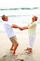 Portrait of a happy mature couple playing on the beach _ Outdoor