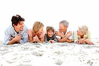 Portrait of a sweet family lying on the sea shore over bright background