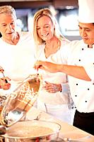 Happy chef serving food to beautiful mature couple