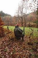 hunter shooter sitting and waiting with the rifle in hand during a battue, Germany