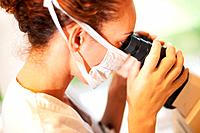 Closeup of young female researcher looking into a microscope