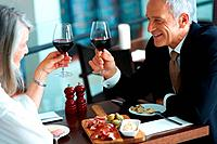 Mature couple enjoying dinner in a restaurant toasting wine glasses