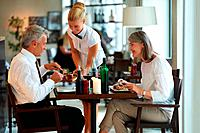 Mature couple at restaurant having dinner being served by a waitress