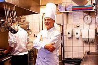Portrait of confident male chef smiling with trainee in kitchen