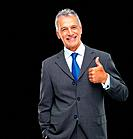 Portrait of male entrepreneur approving by making thumbs up sign on black background