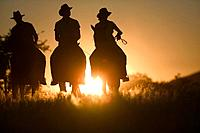 Silhouette of Three Riders Against Sunrise
