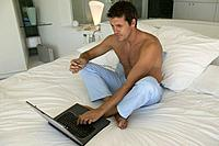 Barechested Man Sitting with Laptop and Credit Card in Bed