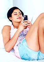 Portrait of attractive young woman texting message while lying in sofa