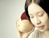 Young Woman with Closed Eyes Listening to Shell
