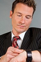 stressed businessman glancing at the watch, Germany