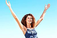 Portrait of attractive young woman enjoying breeze against sky with arms outstretched