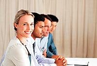 Portrait of smiling female executive sitting beside colleagues during board meeting