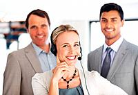 Portrait of happy business woman in headphones smiling with colleagues in background