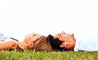 Side view of happy couple lying on grass together _ copyspace