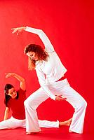 Two women practicing yoga, red background