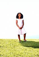 Beautiful African American girl smiling while standing in grass