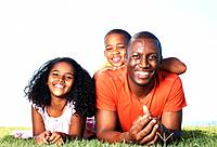 Portrait of happy African American father enjoying with children in park while lying on grass