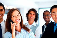 Portrait of beautiful business woman using cell phone with colleagues in background